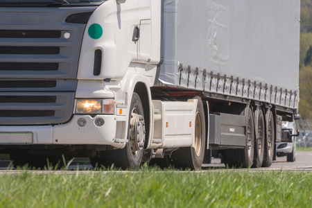 Truck with semi-trailer driving in the spring in freight traffic Archivio Fotografico - 106955540