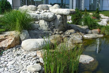 Water feature design, two-tiered patio pond built with stone boulders.