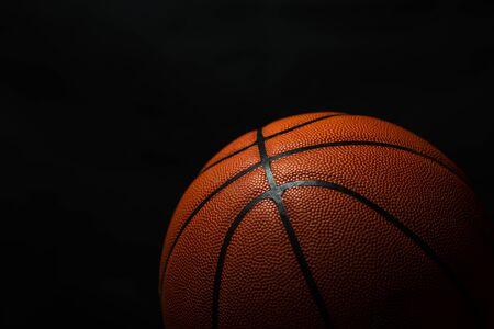 Basketball unter dem Licht mit schwarzem Hintergrund