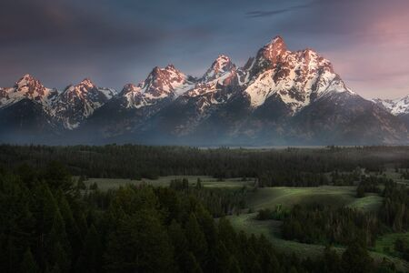 A view overlooking the Grand Tetons mountains with fog rolling through the valley