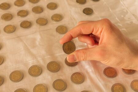 The collector of coins. A man considers two euro coin.