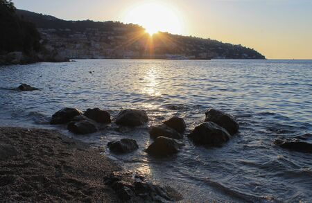 View of Porto Santo Stefano, Tuscany, Italy at sunset from Cantoniera beach with stones on foreground 版權商用圖片