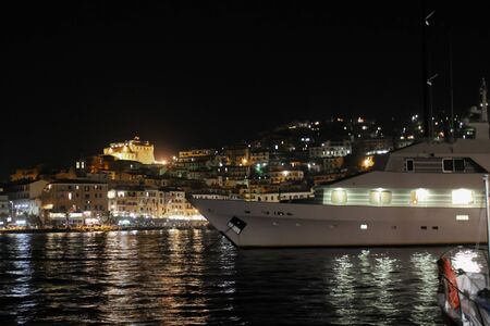 Night view of Porto Santo Stefano, Tuscany, Italy with a yacht on foreground 版權商用圖片