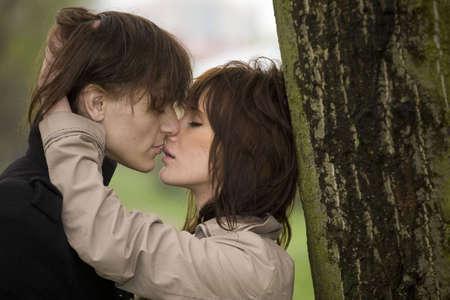 baiser amoureux: jeunes kissinf couple romantique pr�s d'un arbre