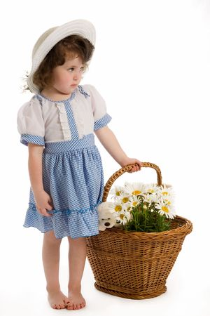 A little beautiful girl with bonnet, with a basket with flowers and toys.  photo