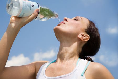 Young woman trinking water outdoors Stock Photo