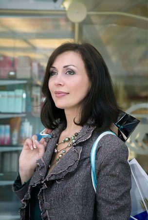 La joven mujer hermosa con compras en almacenamiento