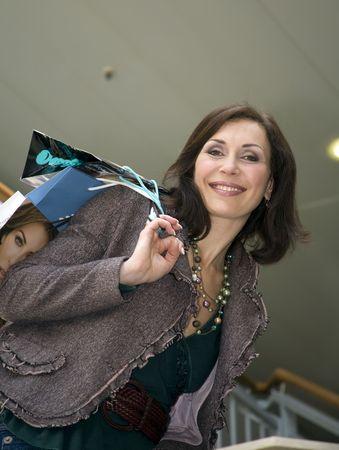 La joven mujer hermosa con las compras de almacenamiento