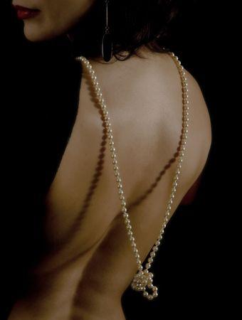EVENING DRESS: CLOUS en marcha de una mujer la espalda con un escote bajo con collar de perlas  Foto de archivo