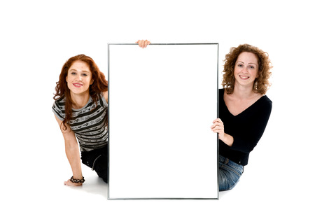 Two red-haired sisters with the big frame posing  in studio. Isolated on the white Stock Photo