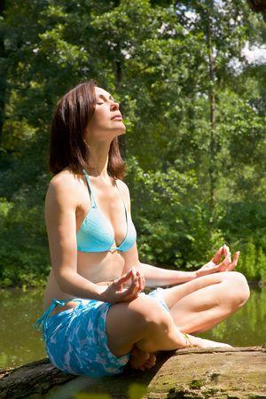 The girl mediteting on coast of wood lake  photo