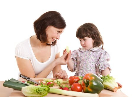 mother and daughter cooking salad at the kitchen photo