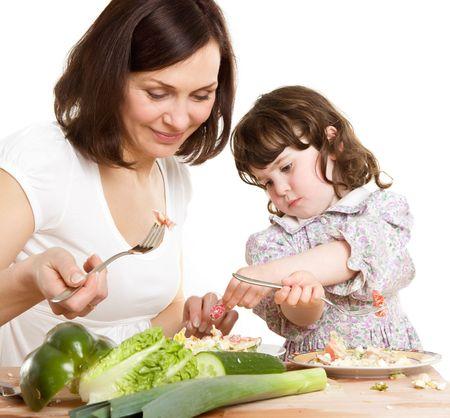 madre e hija que cocinan la ensalada en la cocina Foto de archivo