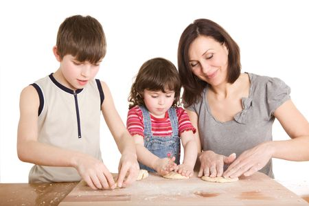 mother and children in the kitchen making a dough Stock Photo
