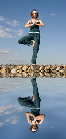 bodyscape: A young woman doing yoga on a stone above  water
