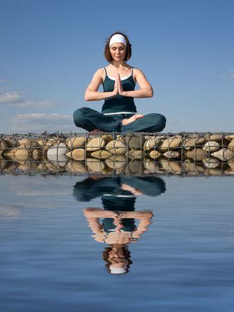 Una joven mujer haciendo yoga en una piedra por encima del agua
