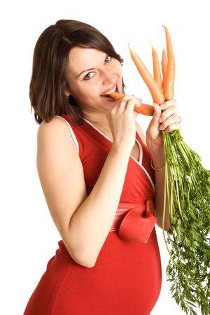 21 semanas feliz mujer embarazada con zanahorias frescas, aislados en blanco  Foto de archivo