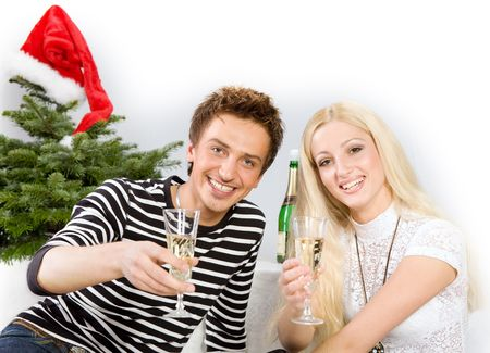 Young beautiful couple in front of Christmas tree cheers with wine photo
