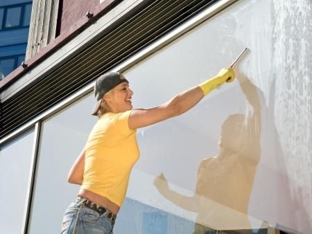 women in yellowT-shirt cleaning a window