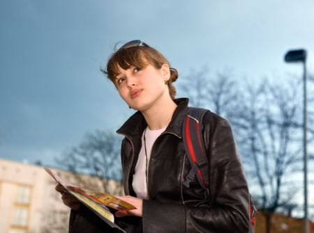 Young woman with city map in hands Фото со стока
