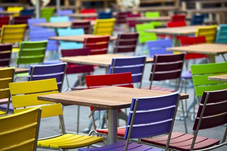 Empty dining tables and coloured chairs in a street cafe photo