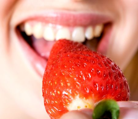 beautiful girl eating a strawberry, isolated on white Stock Photo - 5431141