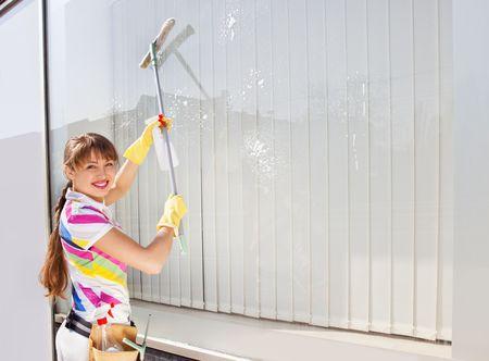 Young woman washing the window photo