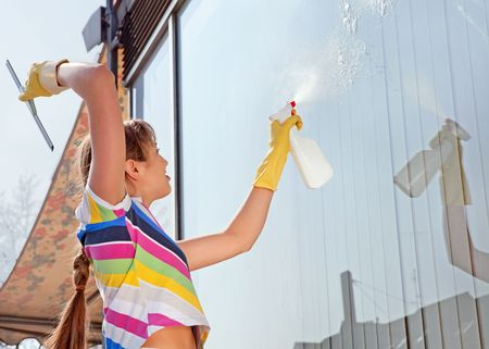Young woman washing the window photo