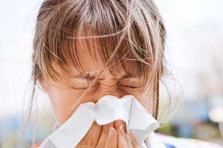 Joven mujer rubia soplando su nariz