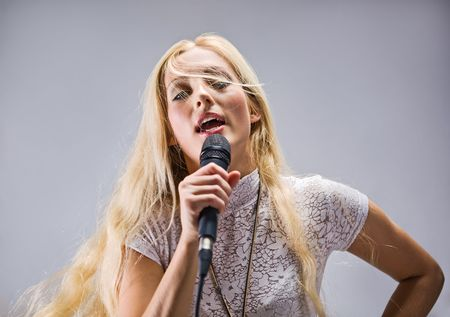 performace: beautiful blond young woman singing into a  microphone