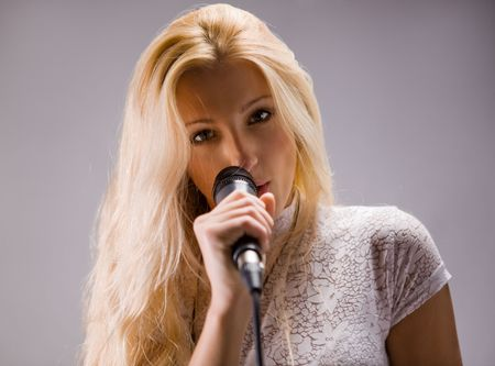 beautiful blond young woman singing into a  microphone Stock Photo - 5924779