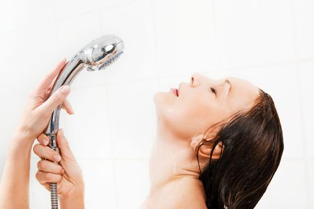 Young smiling woman taking a shower