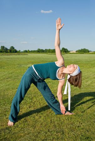 Woman making Yoga exercises in top of a stone wall photo