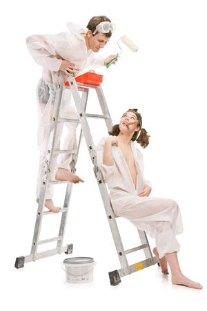 Attractive young adult couple painting interior wall of house, isolated on white photo
