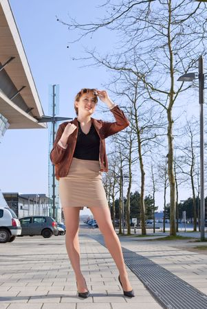 Young cheerful woman stands on street in town photo