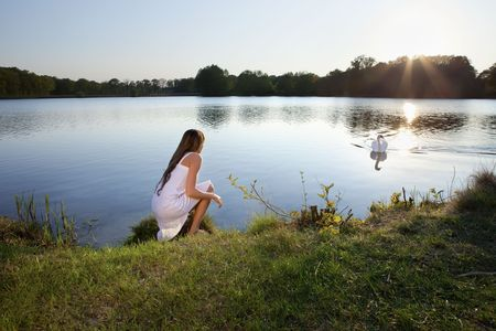 cute blond woman on water background and swan photo