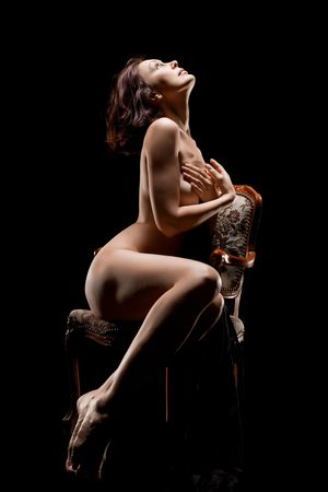 naked woman sitting on old chaur, low key photo  on black