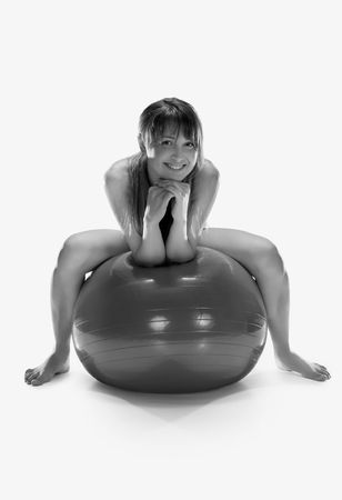 beatiful woman sitting on ball, isolated on white