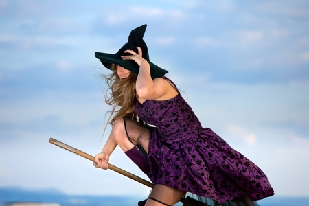 bewitched: pretty witch with hat and broom Stock Photo