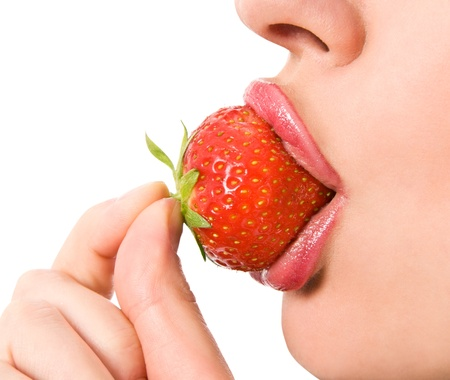 Closeup of a young girl mouth with a strawberry photo