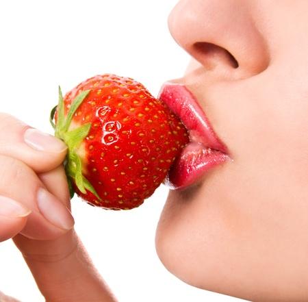 Detalle de una boca chica joven con una fresa Foto de archivo