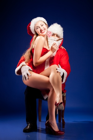 sexy young man: Santa Claus with sexy girl in Santa hat.  Stock Photo