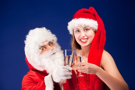 Santa Claus with sexy girl in Santa hat.  Stock Photo