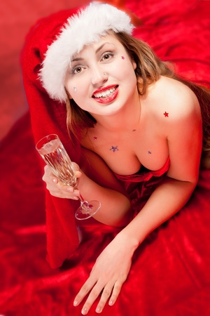 Girl wearing santa clothes with champagne glass photo