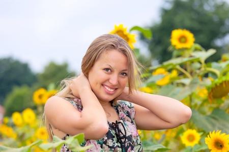 beautiful woman between sunflowers photo