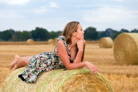 Woman  sitting on hay bale photo