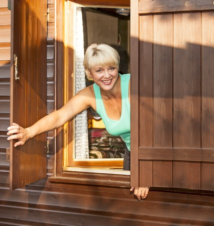 see through: woman looking out the window of a cottage Stock Photo