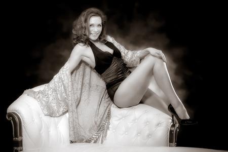 Beautiful adult sexy woman sitting on chair Stockfoto