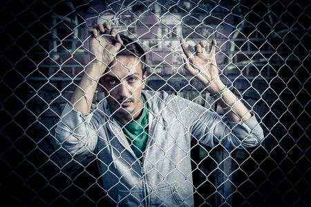 behind: a young sad man behind bars close.