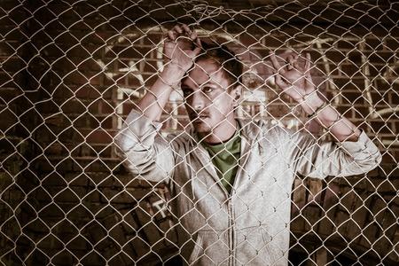 behind bars: a young sad man behind bars close.